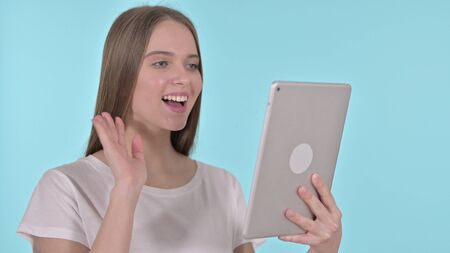 Video Chat on Tablet by Young Woman, Blue Background