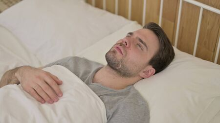 Upset Young Man Thinking in Bed