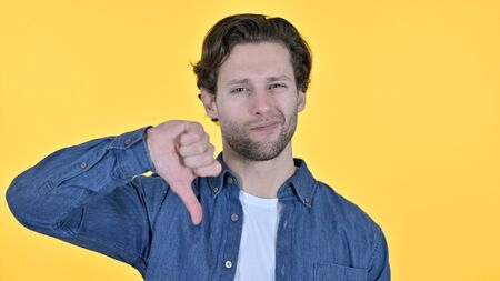Thumbs Down by Disappointed Young Man on Yellow Background
