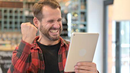 Portrait of Beard Young Man Celebrating Success on Smartphone