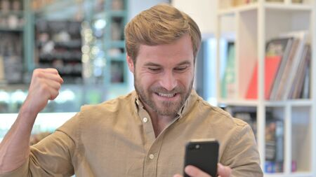 Portrait of Young Man Celebrating Success on Phone