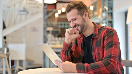 Happy Young Man Excited by Success on Tablet in Cafe