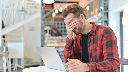 Surprised Beard Young Man in Shock by Loss in Cafe Standard-Bild