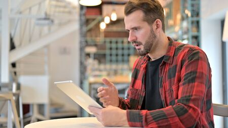 Beard Young Man in Shock while Using Tablet in Cafe Standard-Bild