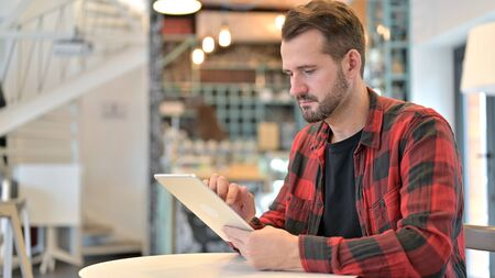 Beard Young Man using Digital Tablet in Cafe