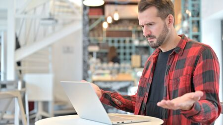Beard Young Man Upset by Loss on Laptop in Cafe