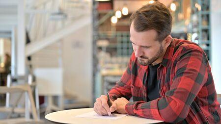 Focused Beard Young Man writing on Paper in Cafe 版權商用圖片