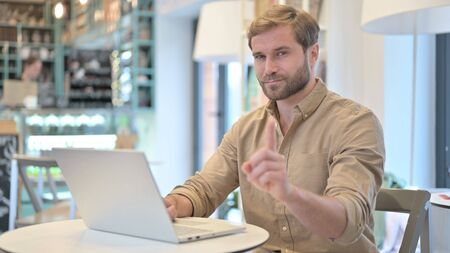 No, Finger Gesture by Young Man with Laptop in Cafe