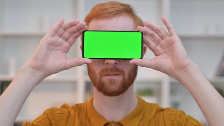 Redhead Man having Smartphone with Chroma Screen over Eyes