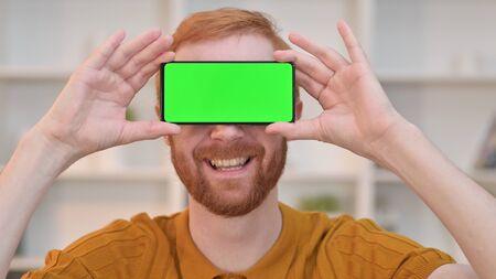 Joyful Redhead Man having Smartphone with Chroma Screen over Eyes