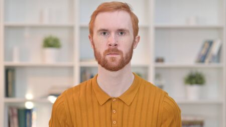 Portrait of Serious Redhead Man Looking at Camera