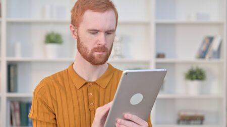 Portrait of Attractive Redhead Man using Tablet 免版税图像