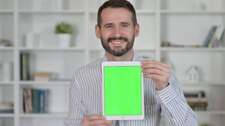 Portrait of Young Man holding Tablet with Chroma Key Screen