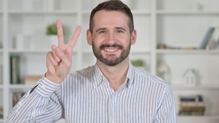 Portrait of Successful Young Man showing Victory Sign 免版税图像