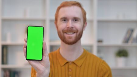Portrait of Redhead Man showing Smartphone with Chroma Screen