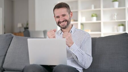 Ambitious Man Celebrating Success on Laptop at Home