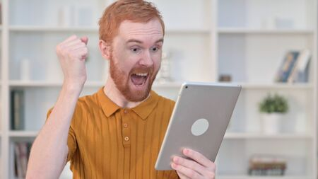Portrait of Redhead Man Celebrating Success on Tablet 免版税图像