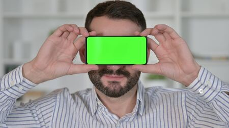 Man with Smartphone with Chroma Key Screen over Eyes 免版税图像