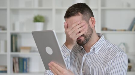 Portrait of Young Man Reacting to Loss on Tablet