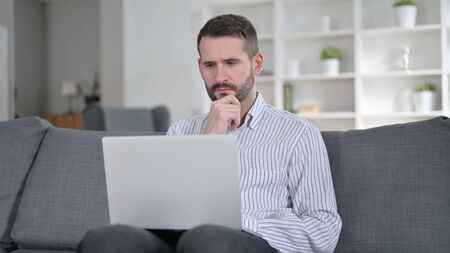 Professional Man Thinking and Working on Laptop at Home