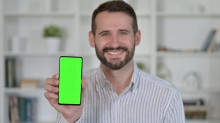 Young Man holding Smartphone with Chroma Key Screen