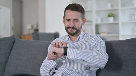 Attractive Young Man using Smart Watch at Home