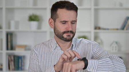 Portrait of Attractive Young Man using Smart Watch
