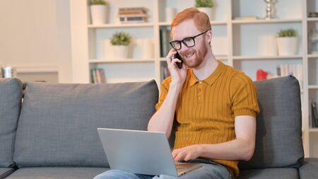 Redhead Man with Laptop Talking on Smartphone at Home