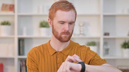 Portrait of Serious Redhead Man using Smart Watch