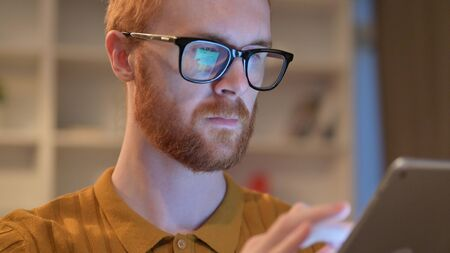 Close up of Serious Redhead Man using Digital Tablet