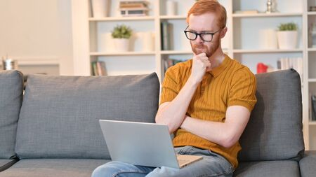 Redhead Man Thinking and Working on Laptop at Home