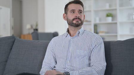 Thinking Young Man Sitting at Home 免版税图像