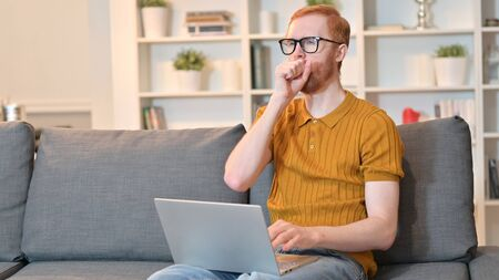 Redhead Man Working on Laptop and Coughing at Home