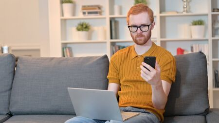 Redhead Man working on Laptop and Smartphone at Home