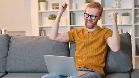 Redhead Man Celebrating Success on Laptop at Home 免版税图像