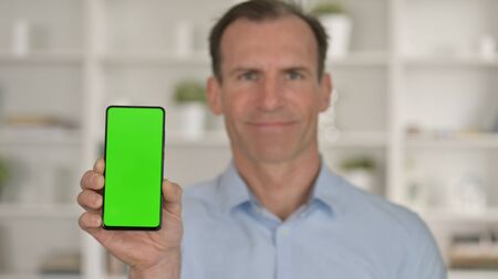 Portrait of Middle Age Businessman holding Smartphone with Chroma Key Screen