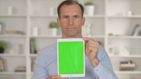 Middle Age Businessman holding Tablet with Chroma Key Screen 免版税图像 - 148658289