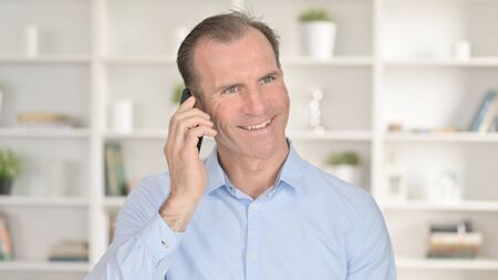 Portrait of Cheerful Middle Aged Businessman Talking on Smartphone