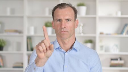 Portrait of Middle Aged Businessman saying No with Finger Gesture 免版税图像
