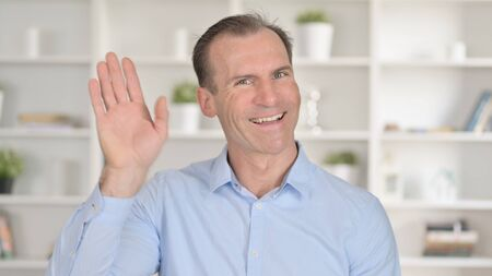 Portrait of Middle Aged Businessman doing Video Chat and Waving 免版税图像 - 148658291