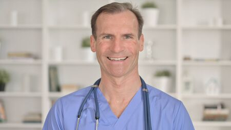 Portrait of Cheerful Middle Aged Doctor Smiling at Camera 免版税图像 - 148658293
