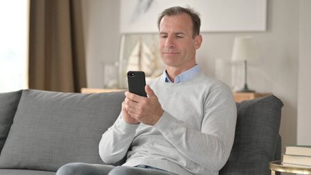 Attractive Middle Aged Businessman using Smartphone on Sofa 免版税图像