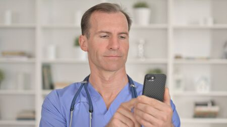 Portrait of Focused Middle Aged Doctor using Smartphone 免版税图像 - 148658298