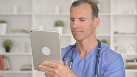 Portrait of Serious Middle Aged Doctor using Tablet