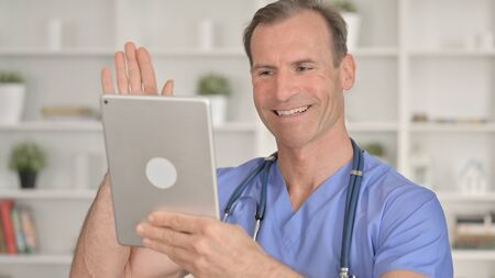 Portrait of Middle Aged Doctor doing Video Chat on Tablet 免版税图像 - 148658381