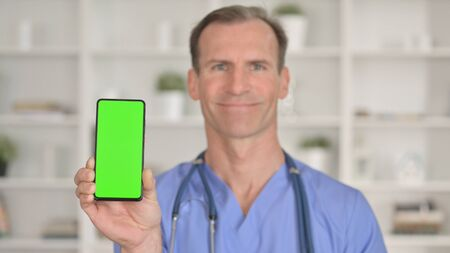 Smiling Middle Age Doctor holding Smartphone with Chroma Key 免版税图像 - 148658380