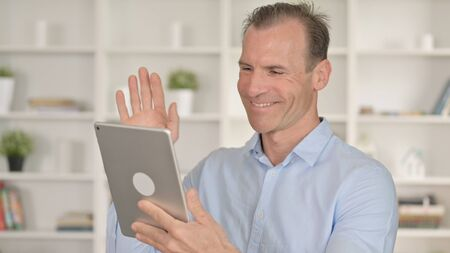 Portrait of Middle Aged Businessman doing Video Chat on Tablet