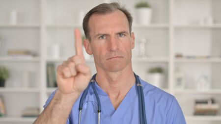 Portrait of Middle Aged Doctor saying No with Finger Gesture 免版税图像 - 148658388
