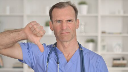 Portrait of Unhappy Middle Aged Doctor showing Thumbs Down 免版税图像 - 148658389