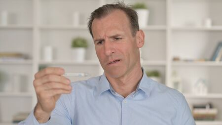 Portrait of Middle Aged Businessman checking Temperature with Thermometer